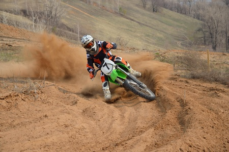 Motocross rider with a strong slope turns sharply on the sandy track with a slipping rear wheel, gritty plume