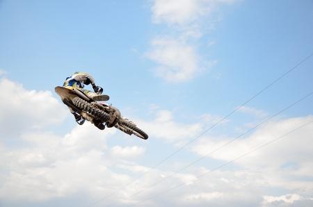super cross: Piloto de motocross en la moto realiza vuelo eficiente es colgando en el aire libre contra el cielo azul