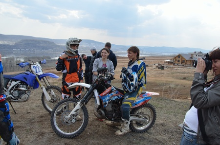 RUSSIA, SAMARA - April 29: Motocross racers group rests on a background of mountains and stormy sky, the girl making sportsmen's photographs the Regional Motocross practice April 29, 2011 in Samara, Russia