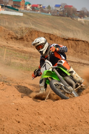 Motorbike racer turns sharply to the on a sandy track a motocross practice in Samara, Russia Stock Photo