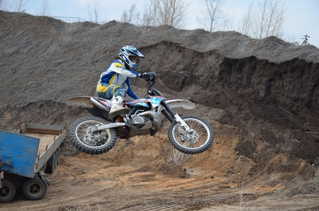Motorbike racer in-flight with large horizontal tilt a high in the air a motocross practice in Samara, Russia Stock Photo - 9981381