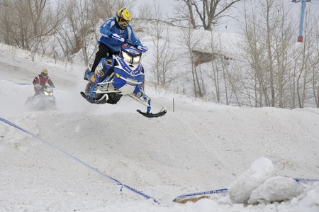 onslaught: RUSSIA, SAMARA - JANUARY 30: Unknown driver on a snowmobile flying down a hill the Russia Championship Snowmobile cross January 30. 2011 in Samara, Russia Editorial
