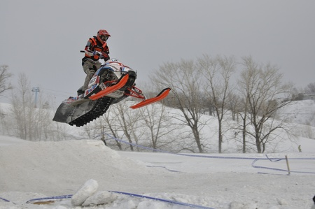 RUSSIA, SAMARA - JANUARY 30: Unknown driver on a snowmobile flying down a hill the Russia Championship Snowmobile cross January 30. 2011 in Samara, Russia Stock Photo - 10005453