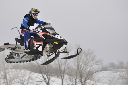 onslaught: RUSSIA, SAMARA - JANUARY 30: An unknown snowmobile racer flying down the mountain the Championship Russia cross snowmobile January 30. 2011 in Samara, Russia Editorial