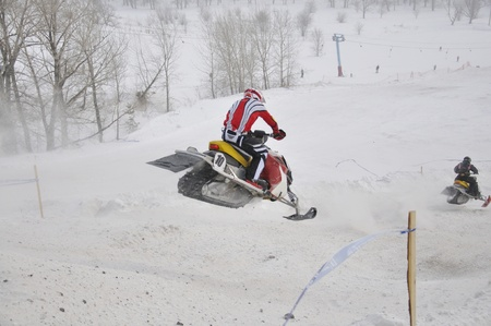 onslaught: snowmobile racer flying down the mountain