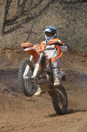 Motocross rider on a motorcycle effectively rides on the rear wheel of a hill  photo