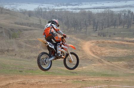 super cross: Corredor de motocross en una moto salta de monta�a grande a la baja en el aire contra el tel�n de fondo de las monta�as y el r�o
