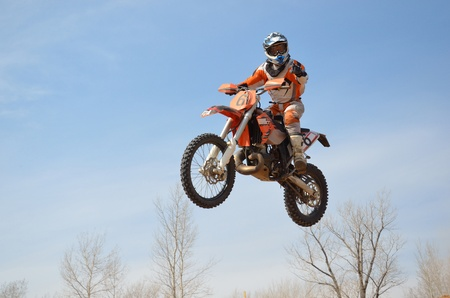 Motocross rider on the motorbike takes off on a high hill ground turned his head facing the camera Stock Photo