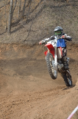 Motocross rider on a motorcycle effectively rides on the rear wheel of a hill