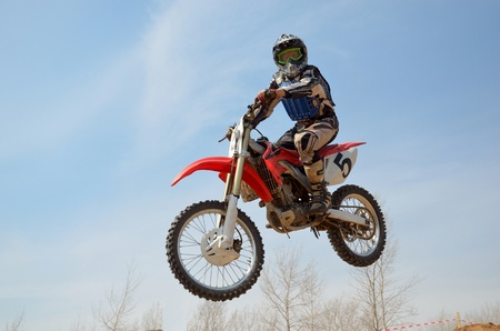 Motocross motorbike racer performs a jump efficient, hangs in the open air Stock Photo