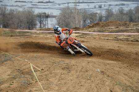 Motorbike racer turns sharply to the on a sandy track a motocross practice