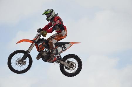 super cross: Motocross Junior piloto en una moto volando por el aire contra el cielo Foto de archivo