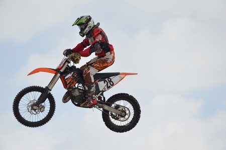 motocross junior rider on a motorcycle flying through the air against the sky