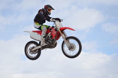 super cross: Jinete de la pr�ctica de motocross realiza un salto efectivo, ubicado en alto en el aire contra el cielo azul