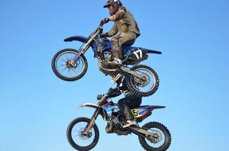 super cross: Jinete de invierno motocross dos realiza un salto en el aire contra un cielo azul