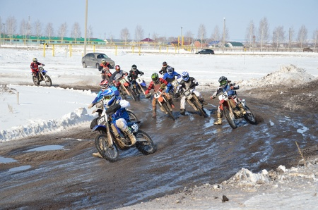 Winter motocross group of riders at the first corner after the start photo
