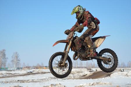 super cross: deportista en la moto vuela por el aire en la limpieza de gafas contra el cielo azul en invierno Foto de archivo