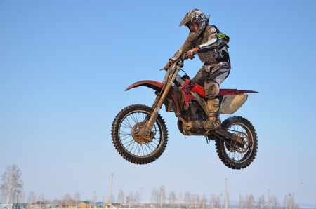 sportsman on the motorcycle flies through the air by clearing goggles against the blue sky in winter