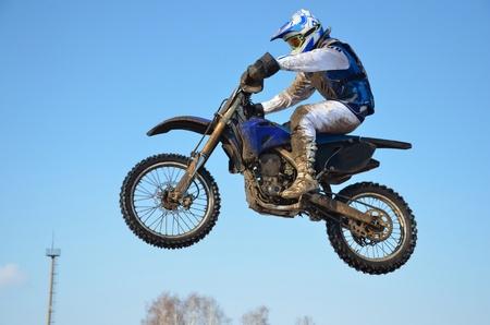 super cross: Conductor en una forma blanca y azul en la motocicleta vuela por el aire, contra el cielo claro
