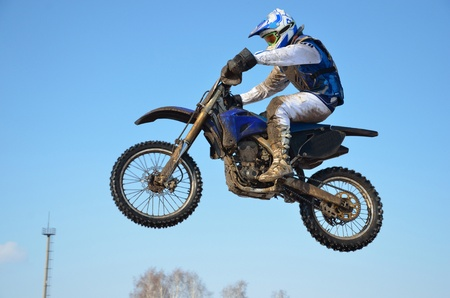 Driver in a white and blue form on the motorcycle flies through the air, against the clear sky Stock Photo - 10815876