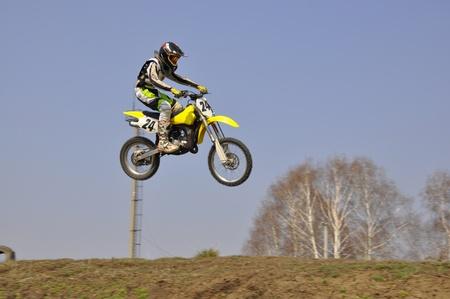 super cross: motociclistas motocross realizan un salto, al aire libre