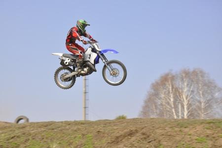 super cross: Motocross del conductor de una motocicleta volando por el aire contra el cielo Foto de archivo