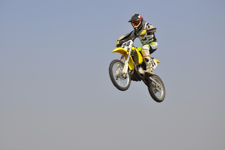 Motocross motorbike racer performs a jump efficient, hangs in the open air photo