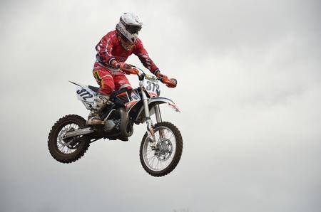 "super cross: RUSSIA, SAMARA, Chapayevsk - 17 de octubre: Un salto sobre la colina, moto racer I. Baranov en el fondo de un cielo tormentoso de la Copa Abierta ""Volga"" motocross el 17 de octubre de 2011 en Chapayevsk, Samara, Rusia"