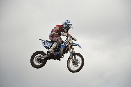 RUSSIA, SAMARA, CHAPAYEVSK - OCTOBER 17: High flight of motorcycle racer A. Guryev on a motorcycle on the background of clouds the Open Cup Volga motocross on October 17, 2011 in Chapayevsk, Samara, Russia