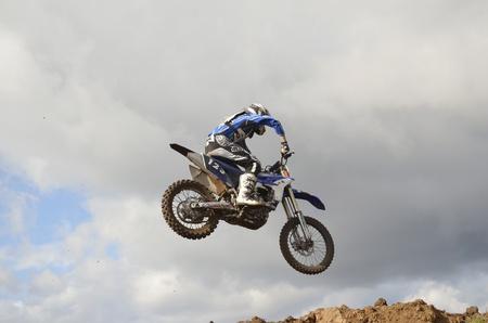 """super cross: RUSIA, Samara, Chapayevsk - 17 de octubre: El espectacular salto de motocross desconocido piloto en el fondo de un cielo tormentoso de la Copa Abierta """"Volga"""" de motocross el 17 de octubre de 2011 en Chapayevsk, Samara, Rusia Editorial"""
