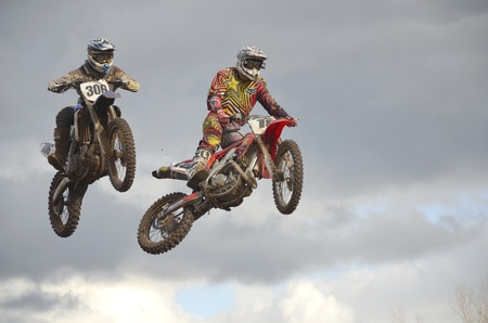 RUSSIA, SAMARA, CHAPAYEVSK - OCTOBER 17: Flying high two motorbike racing unknown against a stormy sky the Open Cup Volga motocross on October 17, 2011 in Chapayevsk, Samara, Russia