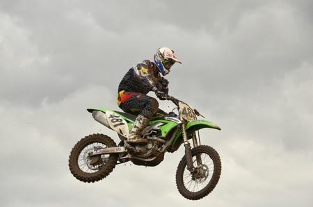 """super cross: RUSSIA, SAMARA, Chapayevsk - 17 de octubre: El espectacular salto de motocross racer S.Astaikin en el fondo de un cielo tormentoso de la Copa Abierta """"Volga"""" motocross el 17 de octubre de 2011 en Chapayevsk, Samara, Rusia"""
