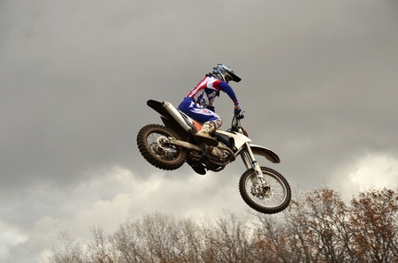 RUSSIA, SAMARA, CHAPAYEVSK - OCTOBER 17: Extreme jump moto racer A.Nikishkin on the background of clouds the Open Cup