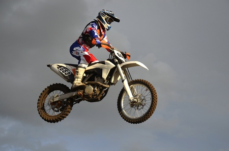 off road racing: The spectacular jump motocross racer on a motorcycle on the background a stormy sky