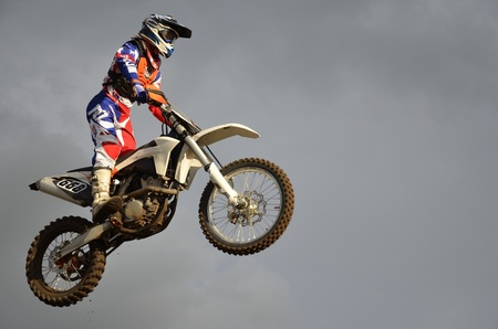 The spectacular jump motocross racer on a motorcycle on the background a stormy sky
