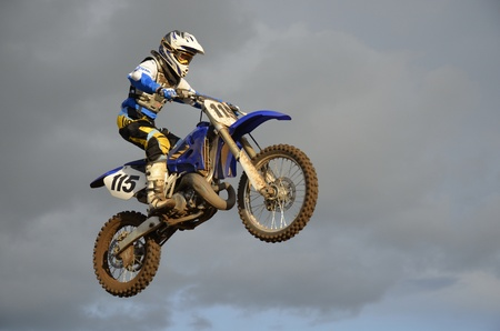 High flight of motocross racer on a motorcycle on the background of clouds