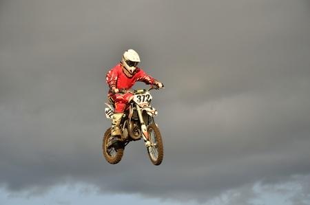 super cross: Un salto por encima de la colina, corredor de motocross en una moto en el fondo de un cielo tormentoso
