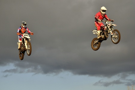 super cross: Volando alto en dos carreras de moto contra un cielo tormentoso Editorial