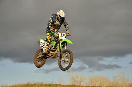 super cross: A saltar por encima de la colina, corredor de motocross en una moto en el fondo de un cielo tormentoso
