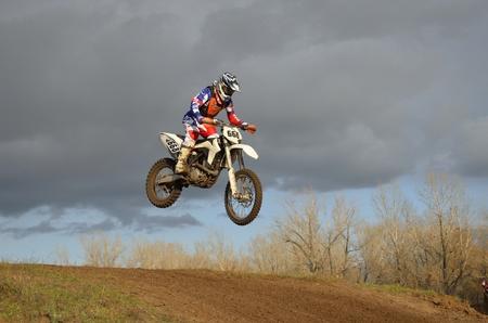 super cross: Un salto sobre la colina, corredor de la motocicleta en una motocicleta en el fondo de un cielo tormentoso