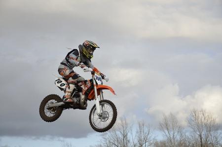super cross: El salto espectacular corredor de motocross en una moto en el fondo de un cielo tormentoso