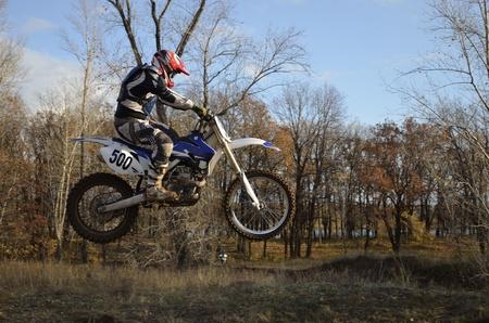 super cross: Un jinete de salto en moto en el fondo de un bosque de oto�o