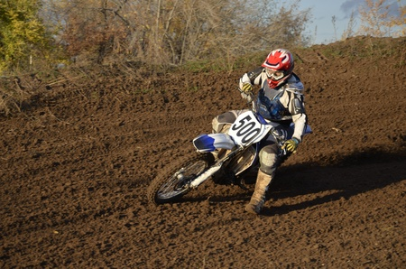 Motocross racer on a motorcycle the turns on a mountain slope with slip