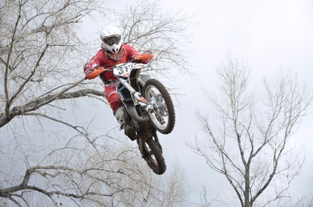 A jump motocross rider on the background an autumn forest photo