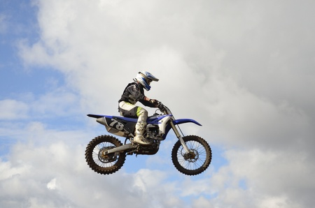 A leap over the hill, motorcycle racer motocross on the background a stormy sky