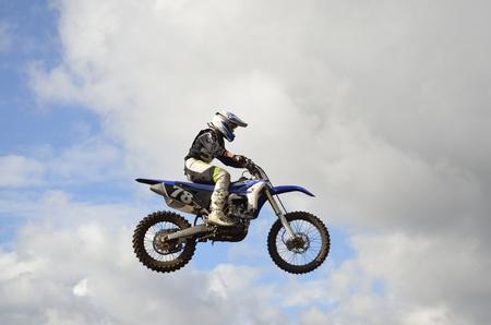 super cross: Un salto sobre la colina, piloto de motos de motocross en el fondo de un cielo tormentoso Foto de archivo