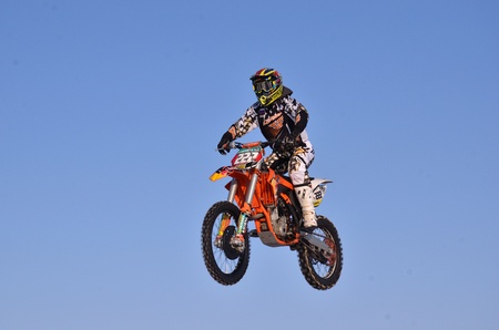 RUSSIA, SAMARA - JANUARY 3: Rider motorcycle D. Vintaev performs a jump in background of blue sky, practice motocross on January 3, 2012 in Samara, Russia