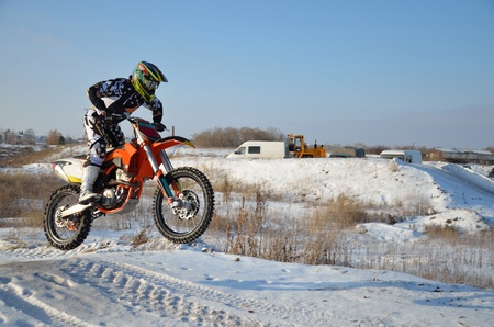 motorcycling: Motorcycling rider on a motorcycle motocross jumps from a hill on a snowy highway