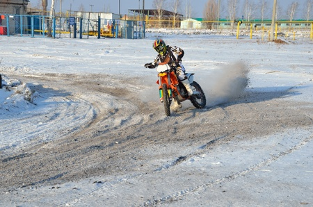 turnabout: Winter motocross, the rider on motorcycle moves in a turnabout with the rear wheel skid on a snowy highway
