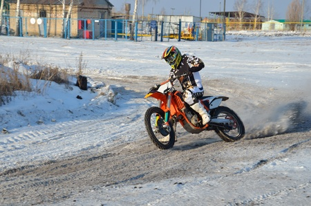 turnabout: Winter motocross, the rider on the motorcycle is accelerating at the exit of a turn on a snow track, with a large rear wheel slip